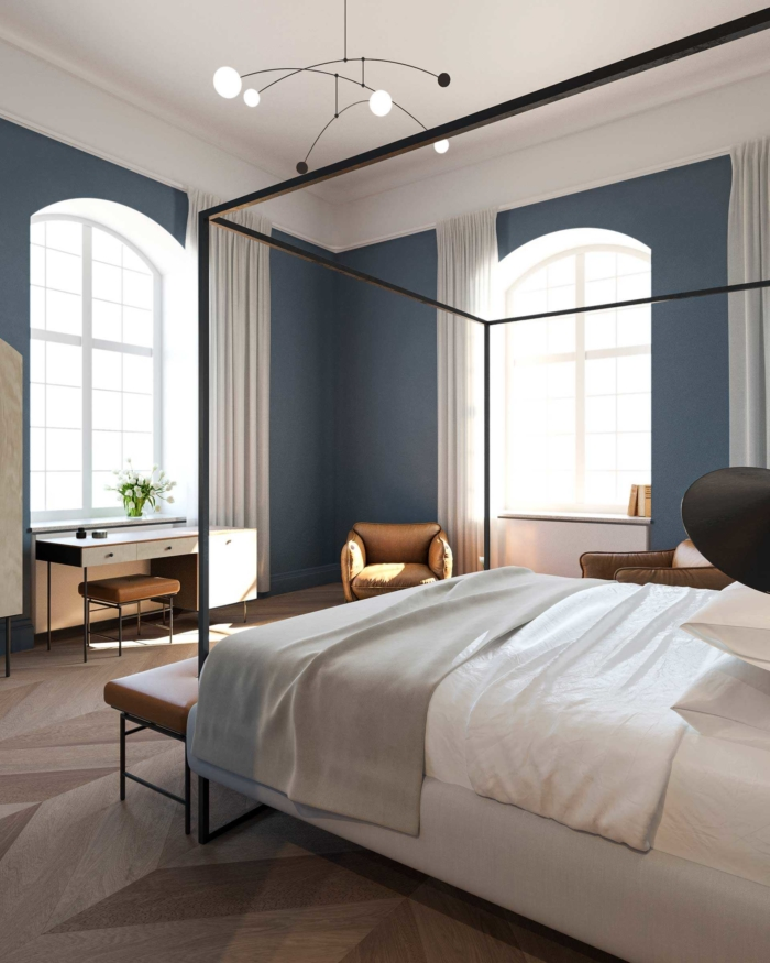 the rooms in nobis hotel copenhagen are painted in saturated blue and green tones with massive chevron patterned parquette and high white painted window